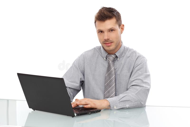 Homem novo que usa o portátil fotografia de stock