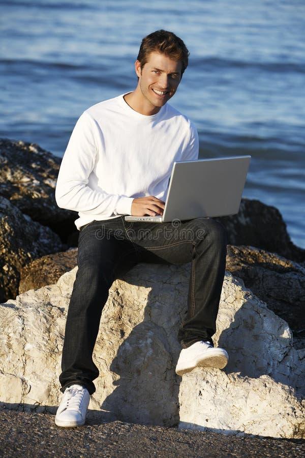 Homem novo que usa o portátil na praia imagem de stock royalty free