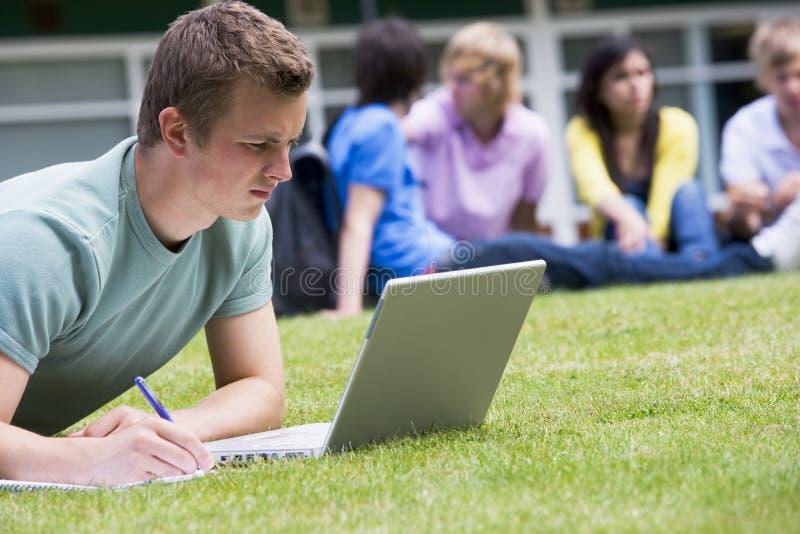 Homem novo que usa o portátil no gramado do terreno foto de stock