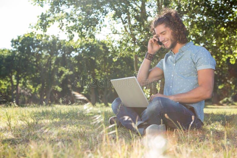 Homem novo que usa o portátil no parque fotos de stock royalty free