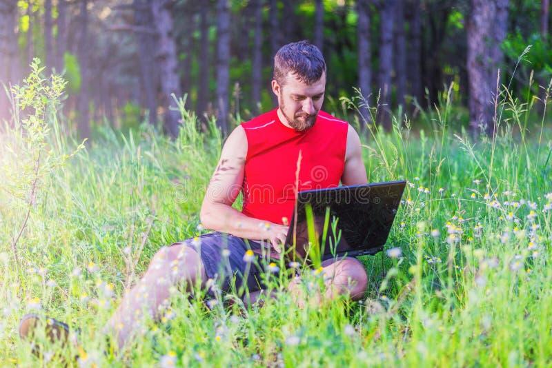 Homem novo que usa o portátil no parque, trabalho remoto imagem de stock