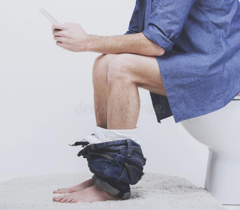 Homem novo que usa o portátil no toalete imagem de stock royalty free