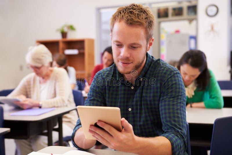 Homem novo que usa o tablet pc em uma classe do ensino para adultos imagem de stock