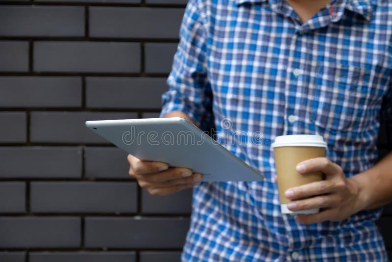 Homem novo que usa o tablet pc que guarda o copo de café na parede da rua com espaço da cópia Homem de negócio ocasional que usa  fotos de stock royalty free