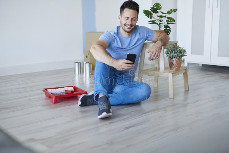 Homem novo que usa o telefone celular durante a renovação de sua casa fotografia de stock