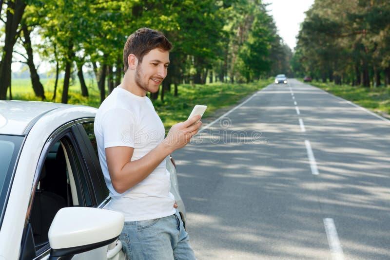 Homem novo que usa o telefone celular perto do carro imagem de stock