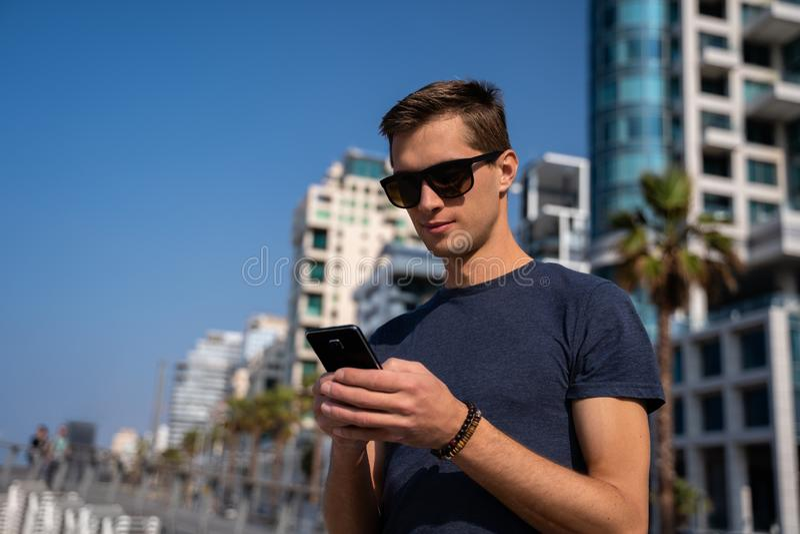 Homem novo que usa o telefone Skyline da cidade no fundo foto de stock