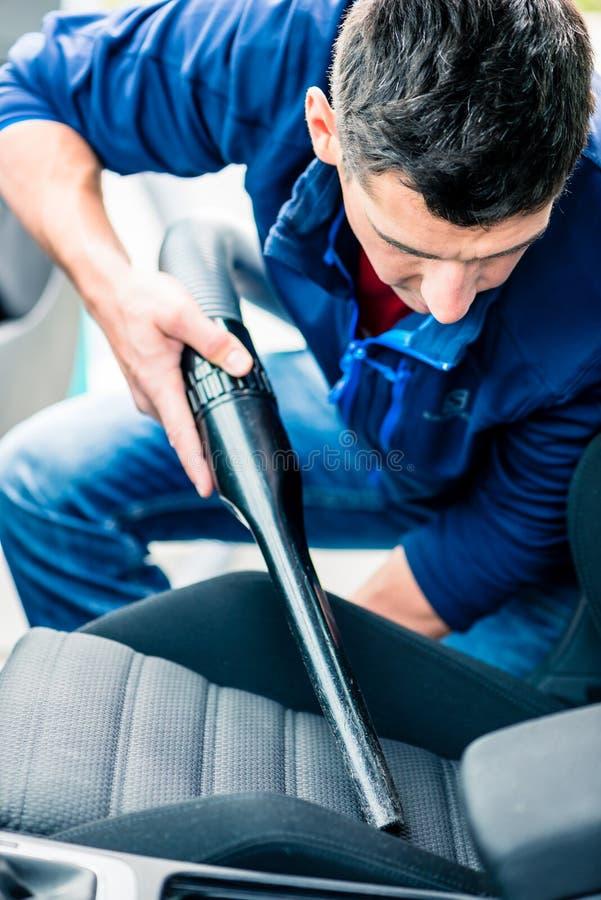 Homem novo que usa o vácuo para limpar o interior de um carro imagem de stock royalty free