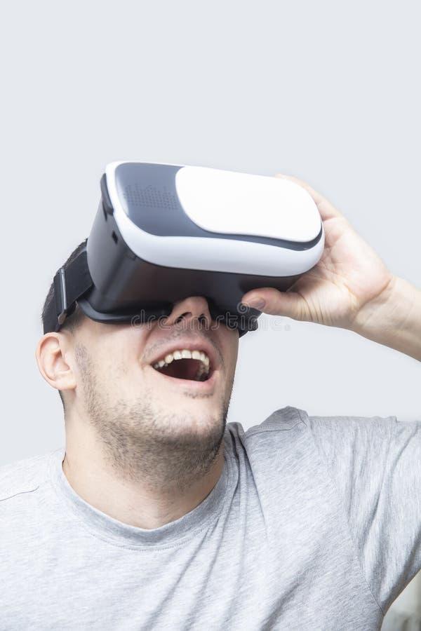 Homem novo que usa os auriculares do vr, experimentando a realidade virtual imagens de stock