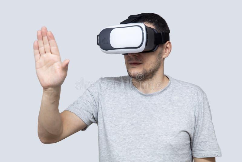 Homem novo que usa os auriculares do vr, experimentando a realidade virtual foto de stock royalty free