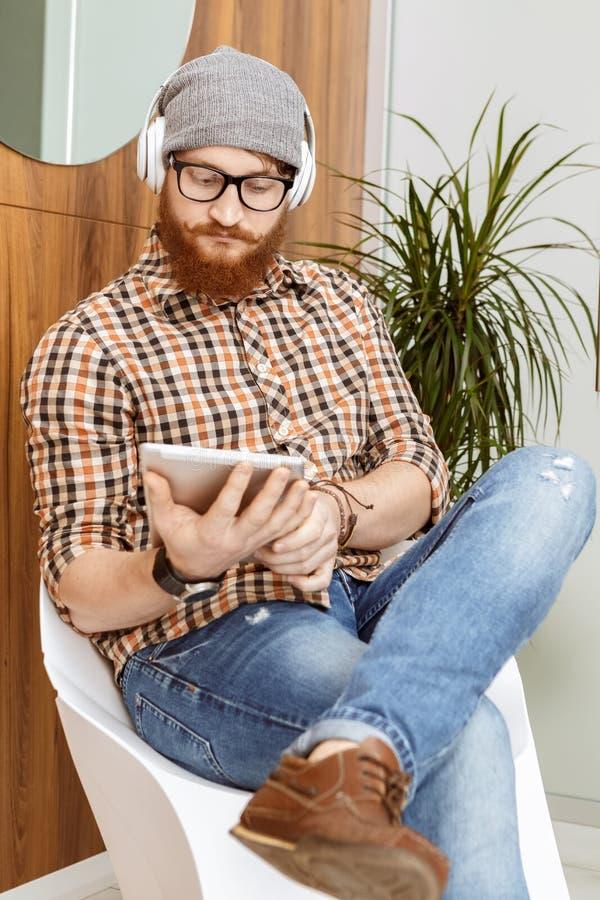 Homem novo que usa sua tabuleta ao sentar-se na cadeira imagem de stock