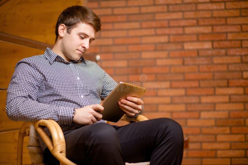 Homem novo que usa sua tabuleta digital com sorriso ao sentar-se na cadeira em casa fotos de stock