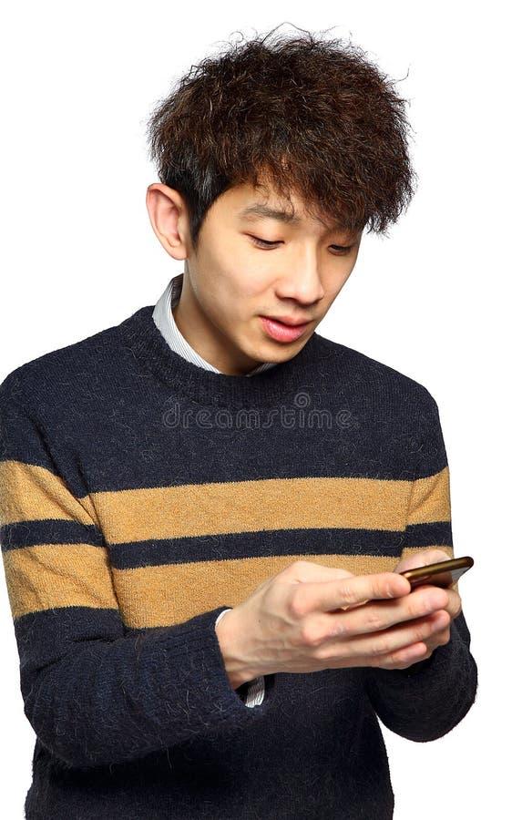 Homem novo que usa texting do telefone celular imagem de stock