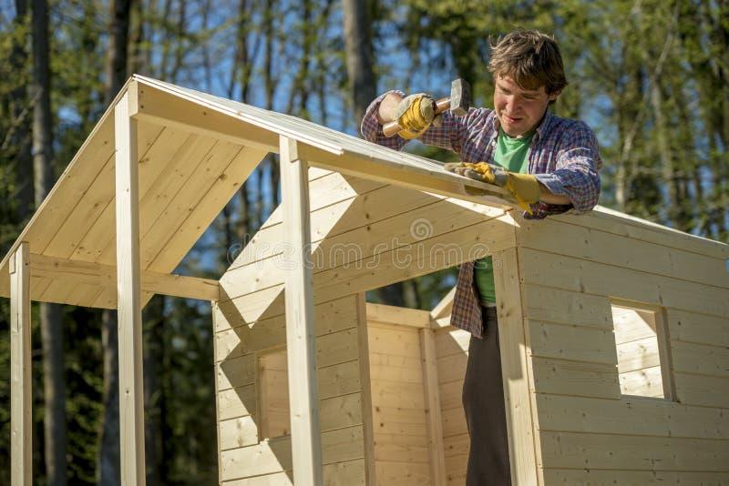 Homem novo que usa um malho para fixar um prego em um telhado de um p de madeira fotos de stock royalty free