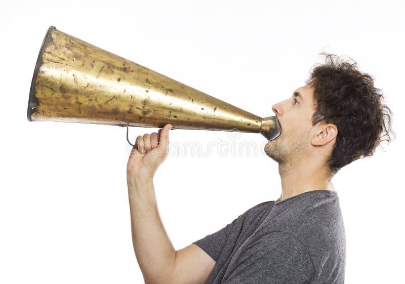 Homem novo que usa um megafone velho fotografia de stock royalty free