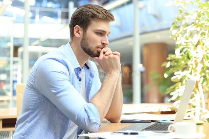 Homem novo que usa um pensamento de assento do portátil em sua mesa como lê a informação na tela imagens de stock