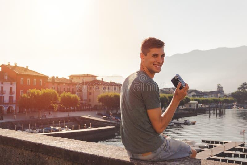 Homem novo que usa uma c?mera do vintage na frente do passeio do lago em Ascona foto de stock