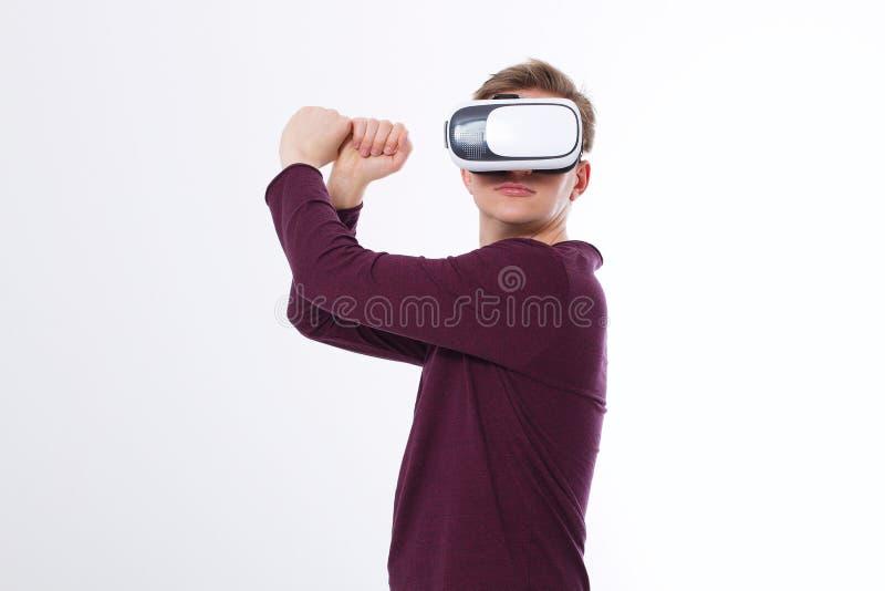 Homem novo que usa uns auriculares de VR e jogando na realidade virtual isolada no fundo branco Copie o espaço e zombe-o acima imagem de stock royalty free