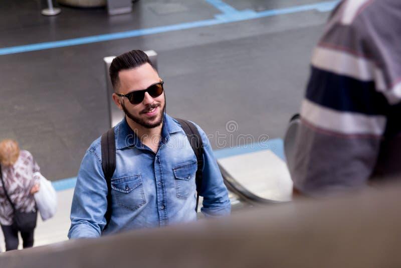 Homem novo que vai acima na escada rolante dentro da estação de metro Conceito o fotos de stock royalty free