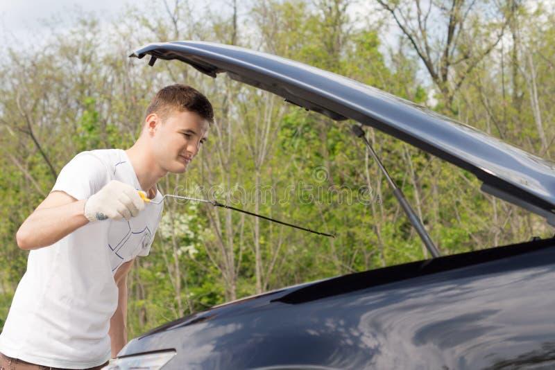 Homem novo que verifica o óleo do motor de automóveis fotos de stock
