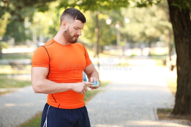 Homem novo que verifica o pulso após o exercício foto de stock