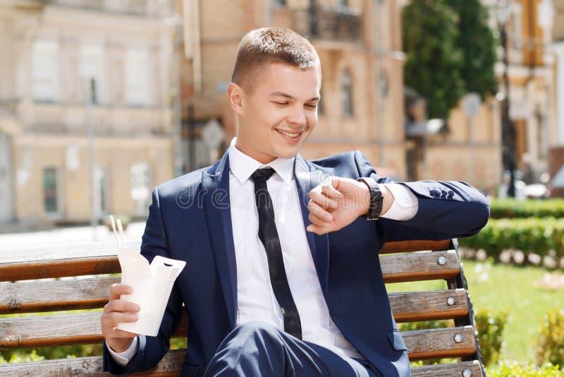 Homem novo que verifica o tempo no parque foto de stock royalty free