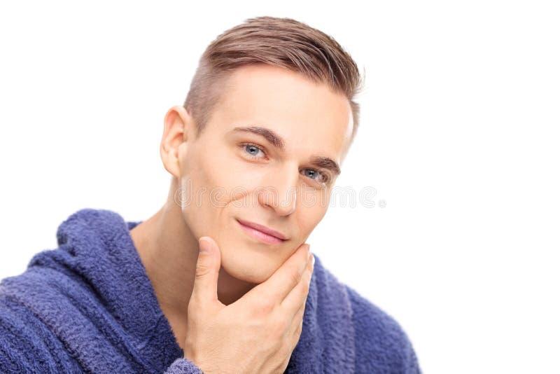 Homem novo que verifica a pele em sua cara imagens de stock