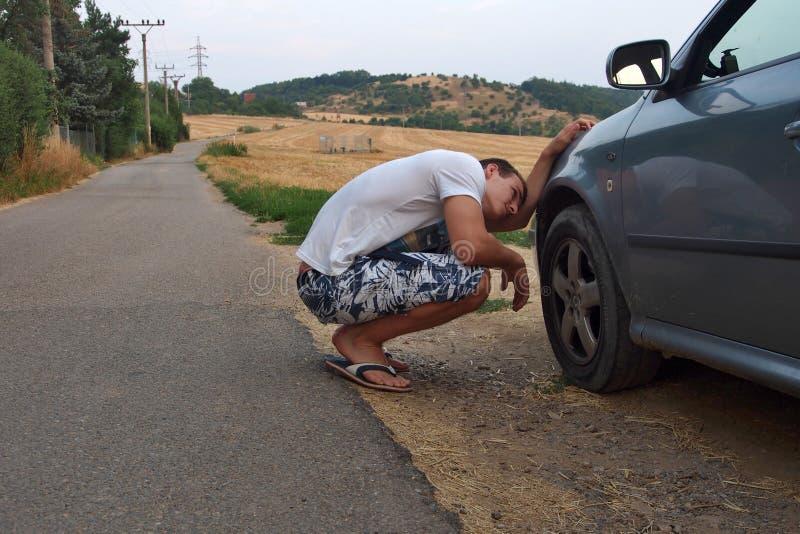 Homem novo que verifica uma roda em seu carro fotos de stock