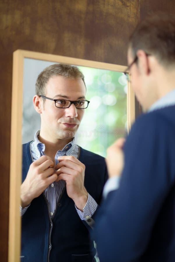 Homem novo que veste acima e que olha o espelho fotografia de stock