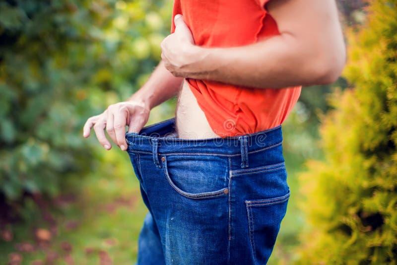 Homem novo que veste calças de brim fracas grandes - conceito da perda de peso imagem de stock royalty free