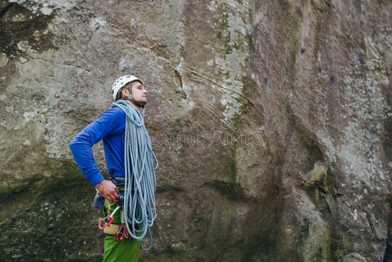 Homem novo que veste no equipamento de escalada com a corda que está na frente de uma rocha de pedra e que prepara-se para escala foto de stock royalty free