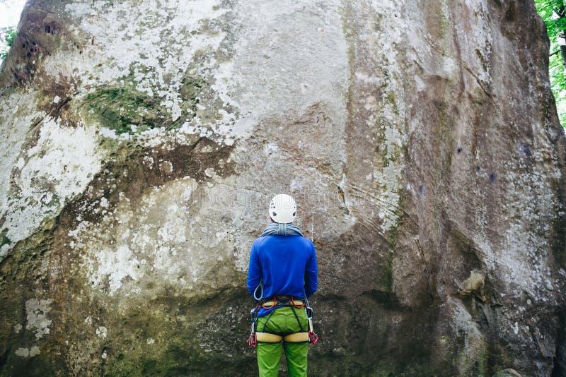 Homem novo que veste no equipamento de escalada com a corda que está na frente de uma rocha de pedra imagens de stock
