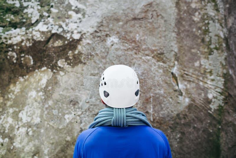 Homem novo que veste no equipamento de escalada com a corda que está na frente de uma rocha de pedra fotos de stock royalty free