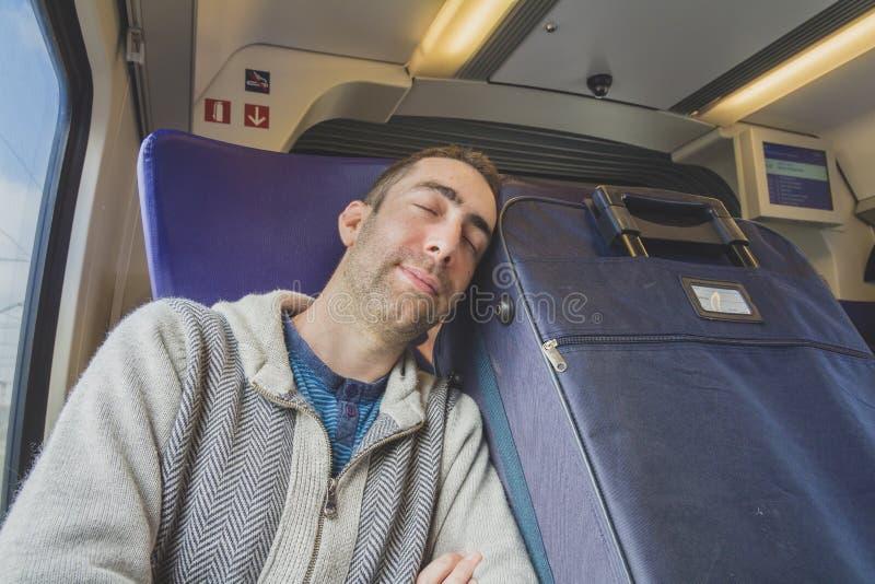 Homem novo que viaja em um trem e em um sono na mala de viagem azul t seguinte imagens de stock
