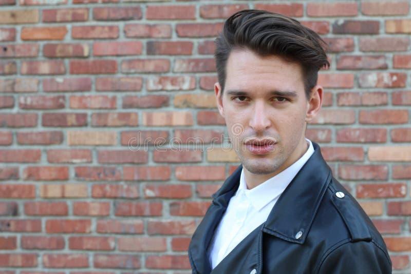 Homem novo relaxado na moda com um corte de cabelo moderno que está contra um fundo azul que olha a câmera, pose dos três quartos fotos de stock royalty free