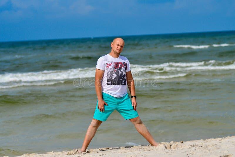 Homem novo relaxado que está na praia imagem de stock