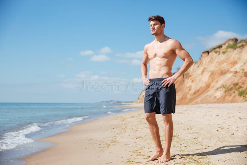 Homem novo relaxado que está na praia foto de stock royalty free