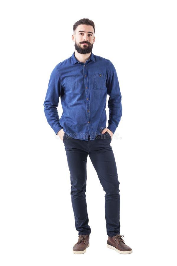 Homem novo relaxado que veste a camisa azul da sarja de Nimes com mãos em uns bolsos que olham a câmera imagens de stock