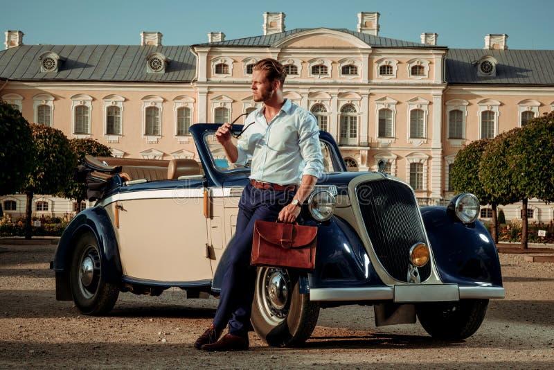 Homem novo rico seguro com a pasta perto do convertible clássico imagem de stock