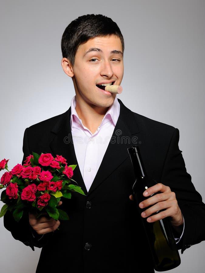 Homem novo romântico considerável com flor cor-de-rosa imagem de stock royalty free