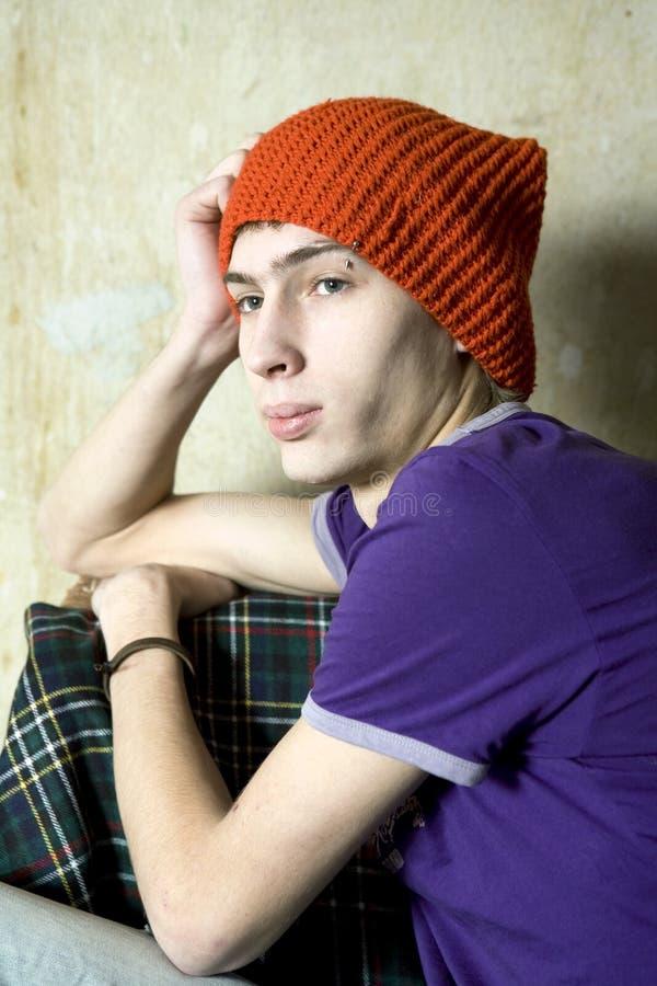 Homem novo sério no chapéu vermelho que senta-se na parede velha imagem de stock royalty free