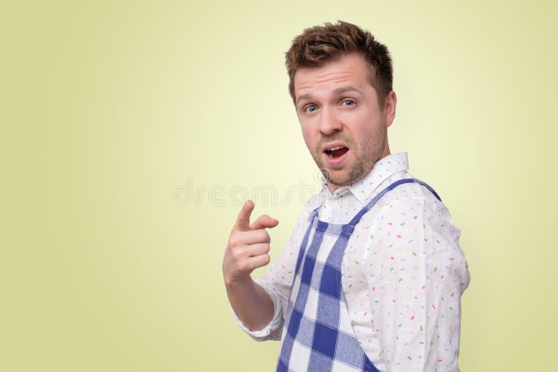Homem novo satisfeito no indicador da exibi??o do avental que aponta em voc? fotografia de stock royalty free