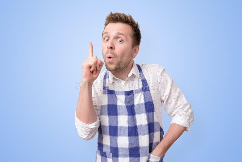 Homem novo satisfeito nos indicadores da exibi??o do avental acima, dando o conselho como cozinhar imagem de stock royalty free