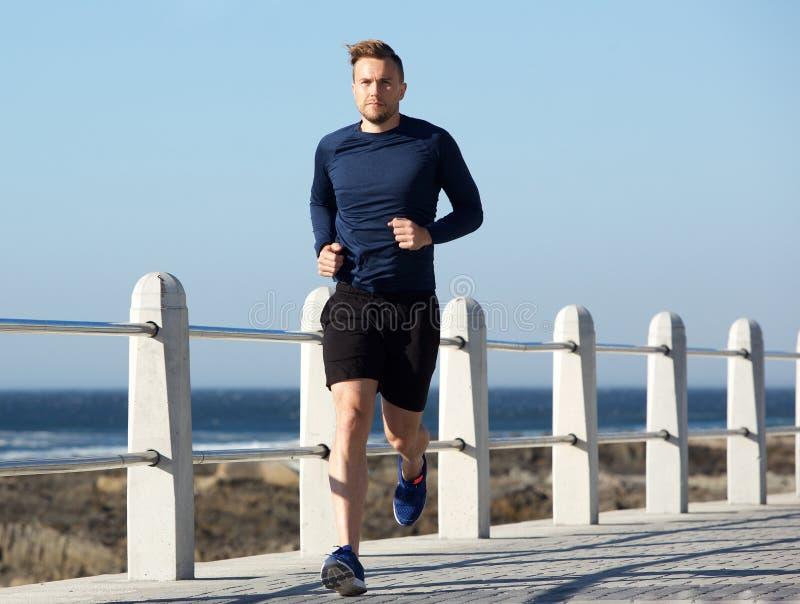 Homem novo saudável que vai para uma corrida fora fotografia de stock royalty free
