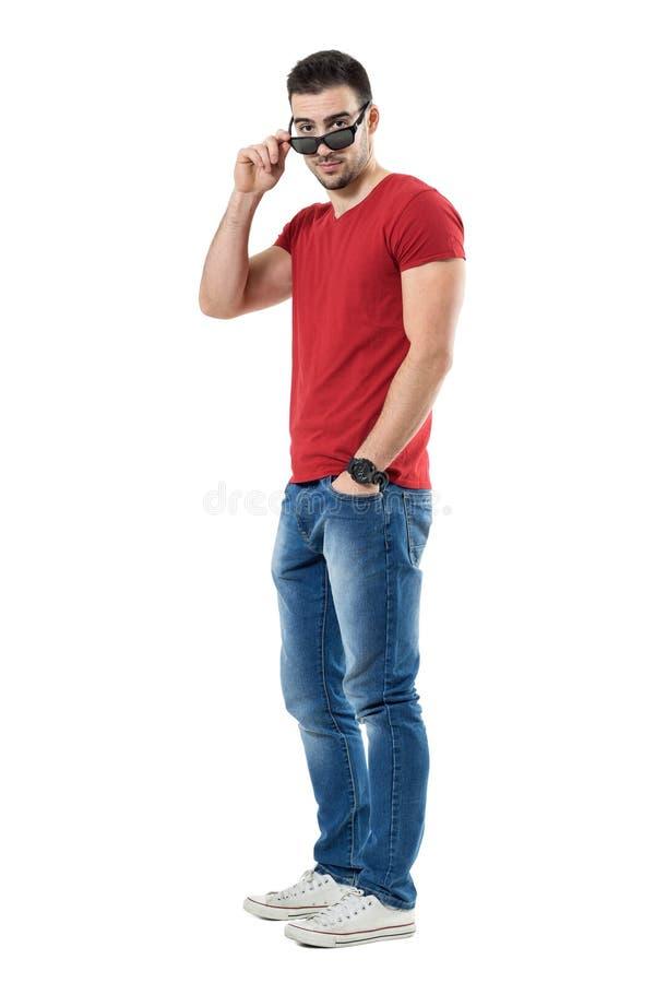 Homem novo sedutor do womanizer que guarda os óculos de sol que olham fixamente na câmera sobre vidros foto de stock
