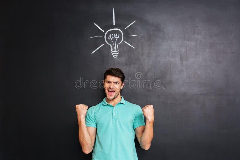 Homem novo seguro feliz que comemora o sucesso e que tem uma ideia fotografia de stock
