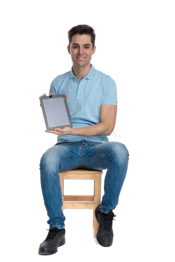 Homem novo seguro que apresenta seus tabuleta e smilin vazios fotografia de stock royalty free
