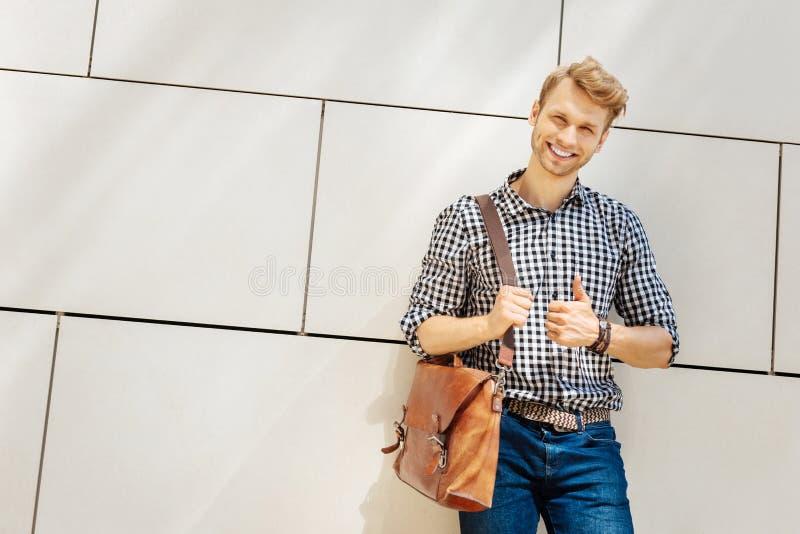 Homem novo seguro que sorri a você imagem de stock