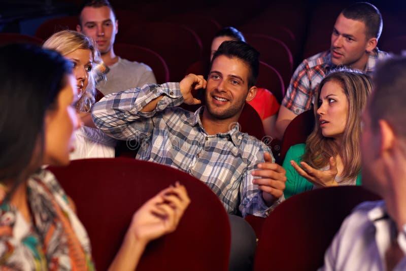 Homem novo seguro que usa o móbil no cinema foto de stock royalty free
