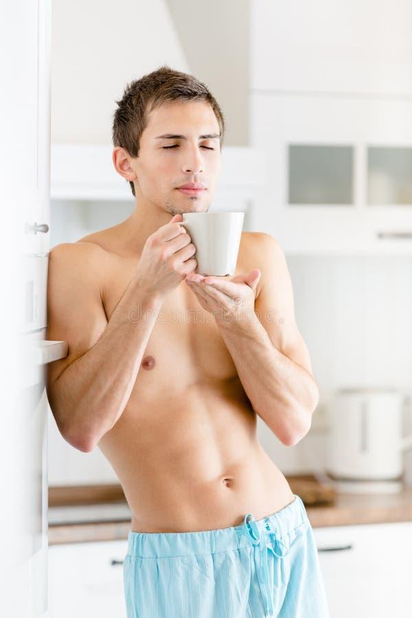 Homem novo semi-nua com a xícara de café na cozinha fotografia de stock